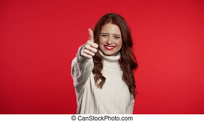 Young woman with red lips making thumbs up sign over colorful background. Winner. Success. Positive girl smiles to camera. Body language.