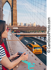 Young woman with red scarf on Brooklyn Bridge