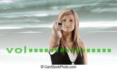 Young woman with remote control changing the volume
