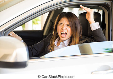 Young woman with road rage - Furious woman in a suit yelling...