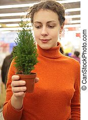 young woman with room plant in store