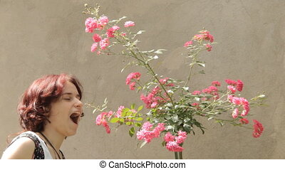 Young woman with rosebush