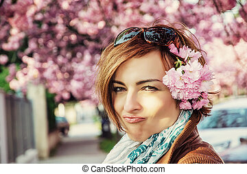 Young woman with sakura flowers, photo filter