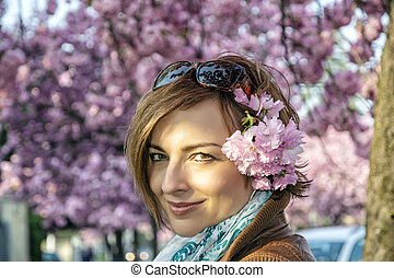 Young woman with sakura flowers