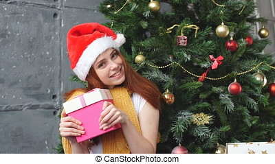 Young woman with santa hat holding a shopping bag.