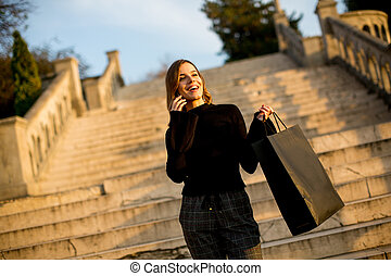 Young woman with shopping bag and mobile phone outdoor