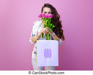 young woman with shopping bag hiding behind bouquet of tulips