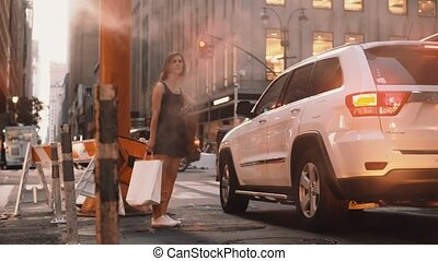 Young woman with shopping bag standing near the smoke pipe in downtown of New York, America near traffic road.