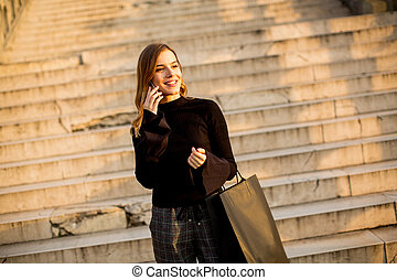 Young woman with shopping bag using mobile phone outdoor