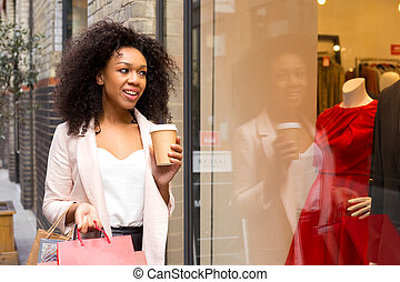 young woman with shopping bags and a coffee
