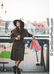 Young woman with shopping bags and coffee