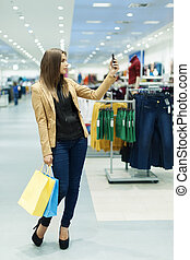 Young woman with shopping bags and mobile phone
