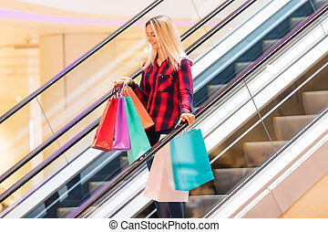 Young woman with shopping bags on escalator in the fashion store