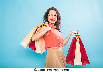 Young woman with shopping bags over blue background