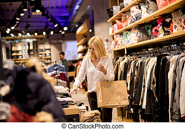 Young woman with shopping bags standing at the clothing store