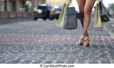 Young woman with shopping bags walking city street