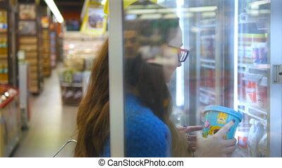 Young woman with shopping cart buying dairy or refrigerated groceries at the supermarket in the refrigerated section opening glass door. Girl taking product from fridge and putting it into the basket