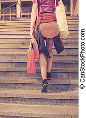 Young woman with shopping walking up stairs - A young woman...