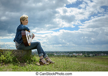 young woman with short blond hair sitting with guitar on the field in cloudy day