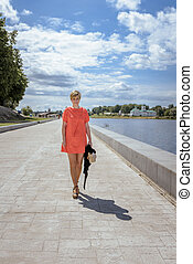 young woman with short haircut in bright dress walking on summer river embankment
