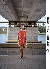young woman with short haircut in bright summer dress standing under a bridge