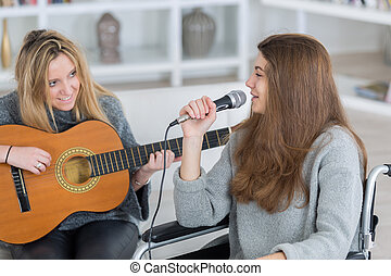 young woman with singing while her friend plays the guitar