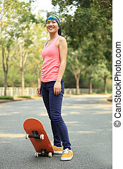 young woman with skateboard in hand