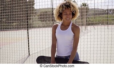 Young woman with skateboard leans against fence