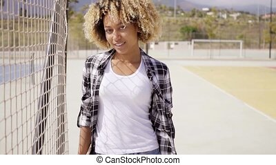 Young woman with skateboard poses by ball court