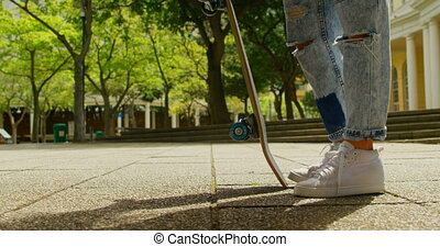 Young woman with skateboard standing in the city 4k