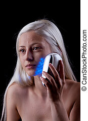 Young woman with skin problems getting phototherapy by blue...