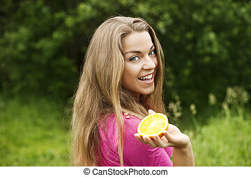 Young woman with slice of orange