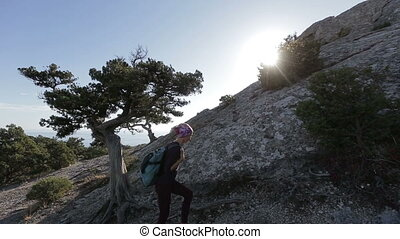 Young woman with small backpack climbing and reaching the top of a mountain. Lady on the summit in beautiful scenery.