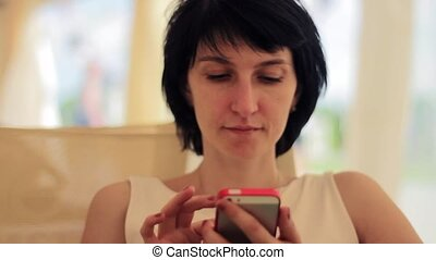 Young woman with smartphone in cafe