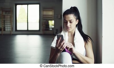 Young woman with smartphone in gym resting after doing exercise.