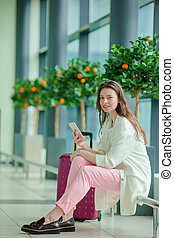 Young woman with smartphone in international airport. Airline passenger in an airport lounge waiting for flight aircraft