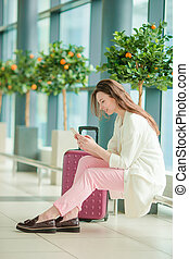 Young woman with smartphone in international airport waiting for flight