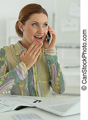 Young woman with smartphone in the office