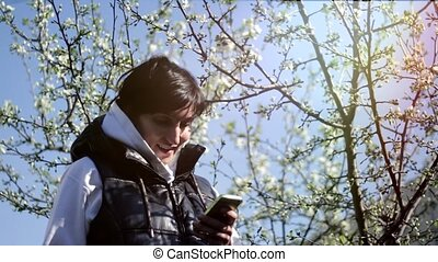 Young woman with smartphone in the park. Spring. Against the background of a flowering tree