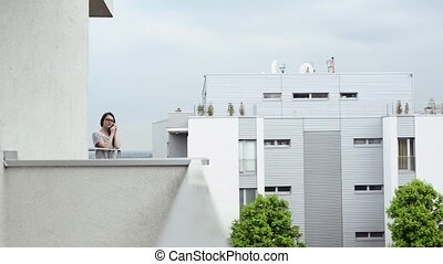 Young woman with smartphone on balcony making phone call.