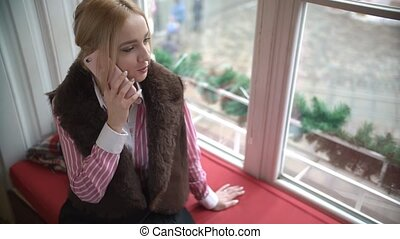 Young woman with smartphone on the window-sill.