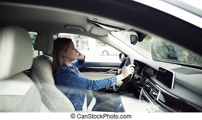 Young woman with smartphone sitting in car, making a phone call.