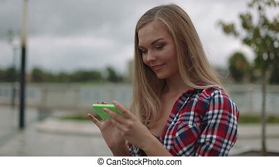 Young woman with smartphone sitting on a bench in the park, close up shot