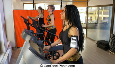 Young woman with smartphone tracker arm strap exercising in...