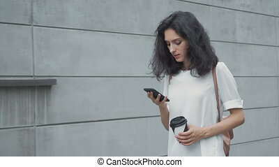 Young woman with smartphone walking in the city, steadicam shot