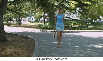 Young woman with smartphone walking in the city