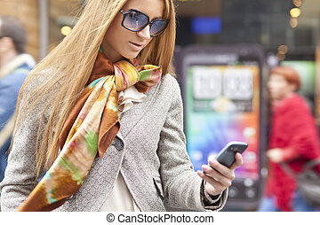 Woman with smartphone walking on street