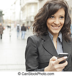 Young Woman with smile and smartphone walking on street
