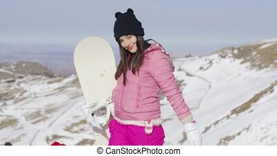 Young woman with snowboard in mountains - Three quarter body...