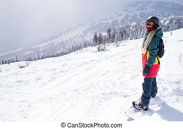 Young woman with snowboard in the mountains walking on a snowy slope.